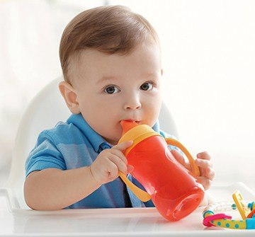 Infant boy chewing on a sippy cup