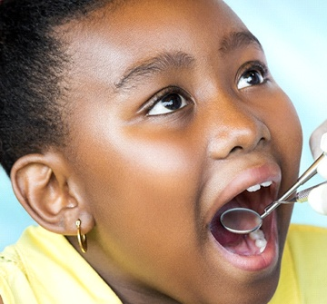 A little girl with gold earrings opening her mouth to show her dentist the problem area of her mouth