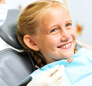 A smiling blonde-haired little girl having her teeth checked at the dentist's office