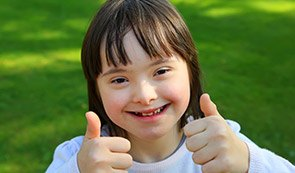 Little girl outdoors giving thumbs up