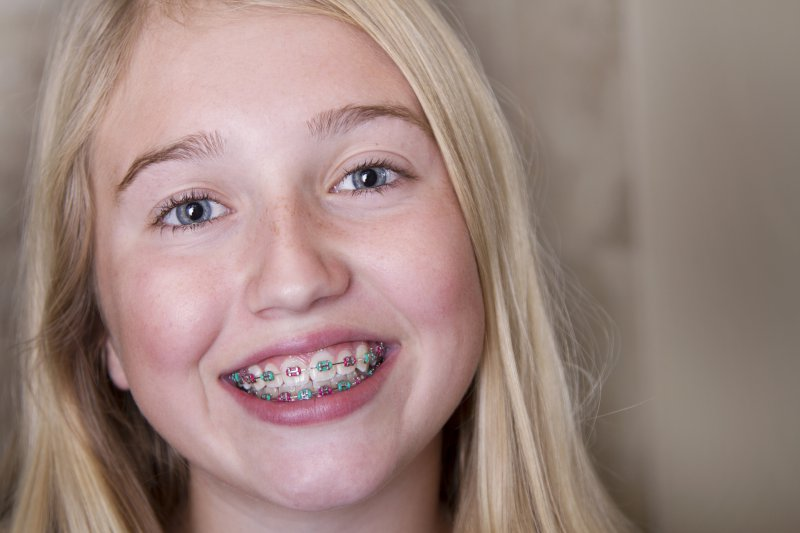 A young child wearing multi-colored braces.