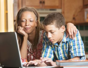 teenager and parent doing research on a laptop