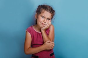 Girl with toothache and poor oral health and school performance