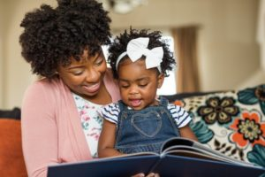 Mother and daughter reading before visiting New Britain children's dentist