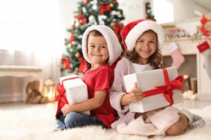 Smiling kids with gifts recommended by New Britain children's dentist