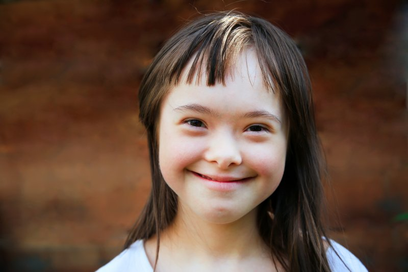 Closeup of young girl with down syndrome smiling